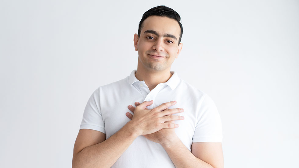 Thankful young man keeping hands on chest