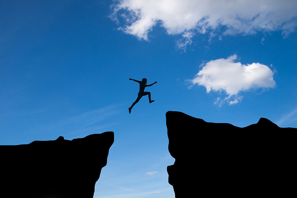 Man jump through the gap between hill.man jumping over cliff on