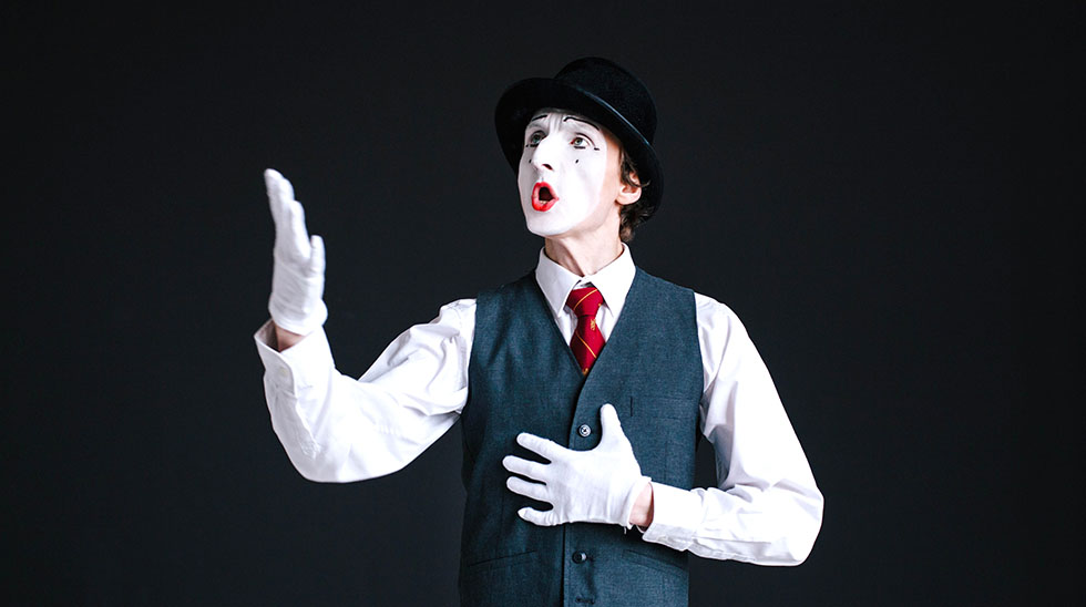 Mime in black sings a song