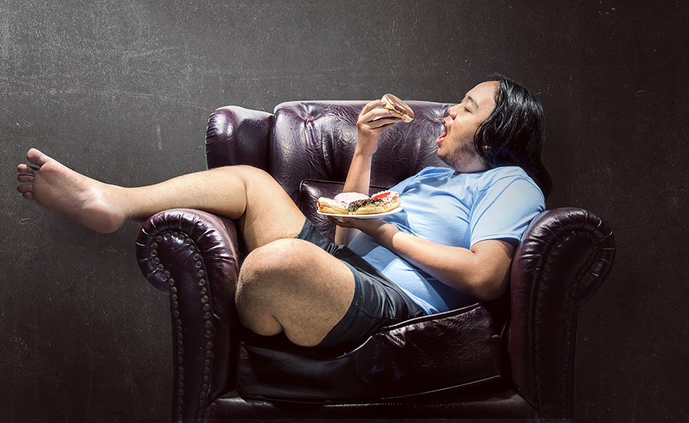 Asian fat man snacking donuts on the couch