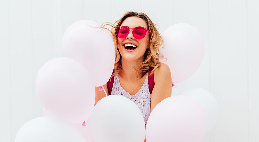 Cheerful girl having fun while holding balloons