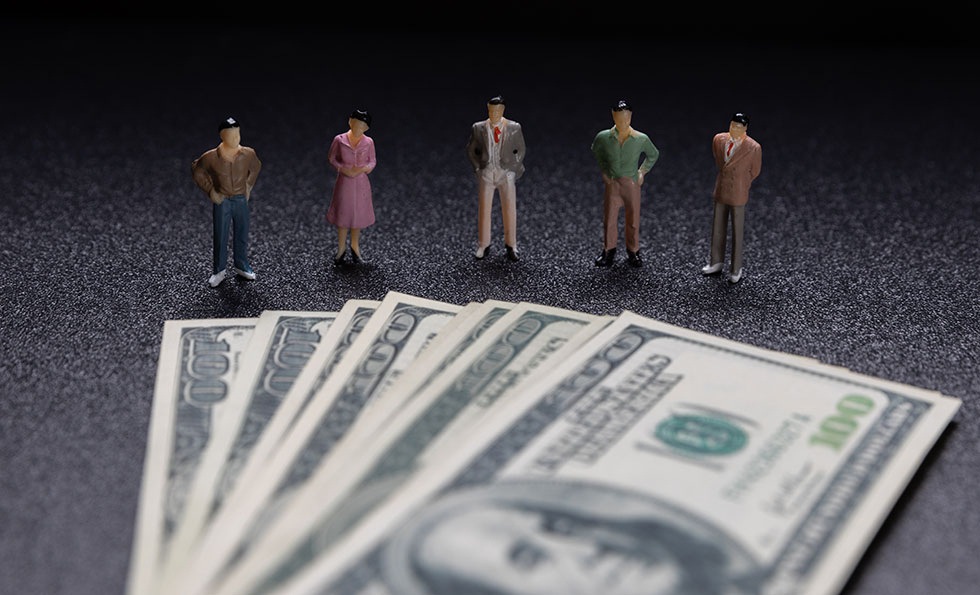 Miniature people: Group of small businessmen standing on coin wi