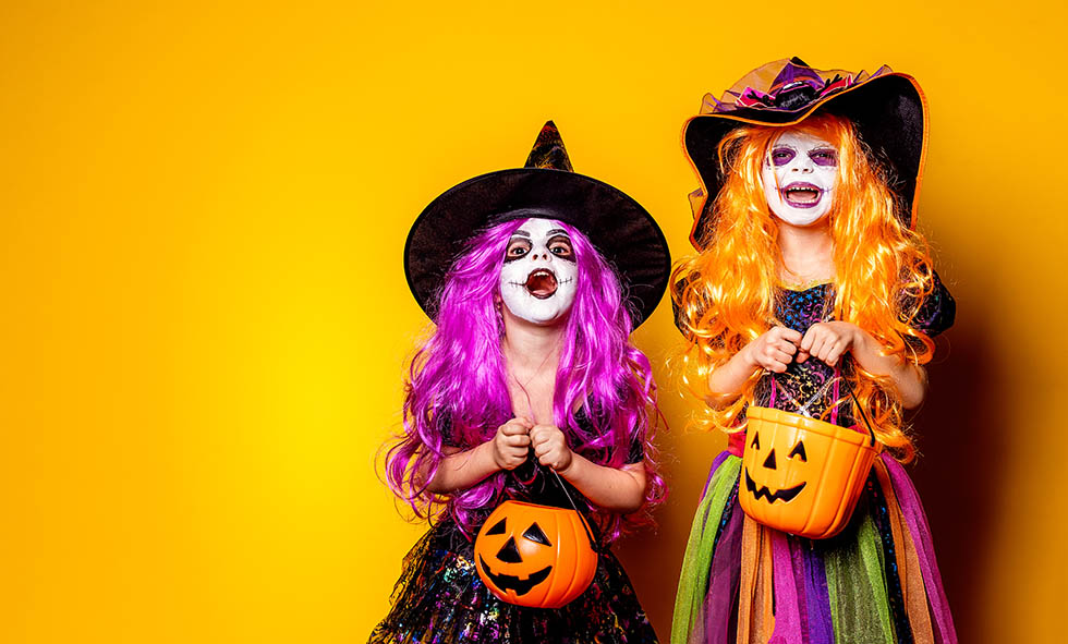 Two Beautiful girl in a witch costume on a yellow background scaring and making faces