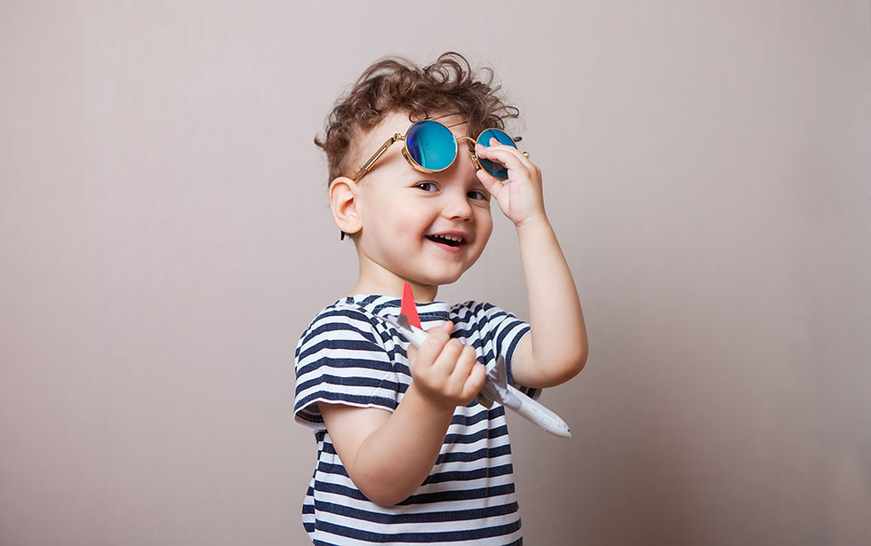 Infant, child with a toy airplane in his hands and sunglasses. R