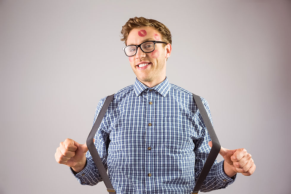Geeky hipster covered in kisses on grey background