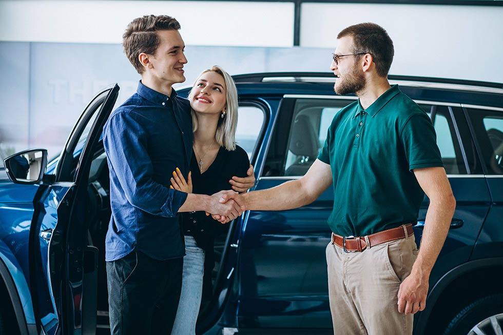 Young family buying a car in a car showroom