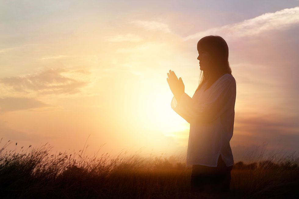 Woman praying and practicing meditating on nature sunset backgro