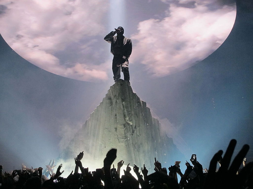 photo - Peter Hutchins. A masked Kanye West performing atop a mountain at the Verizon Center on November 21, 2013 in Washington, D.C. on The Yeezus Tour.
