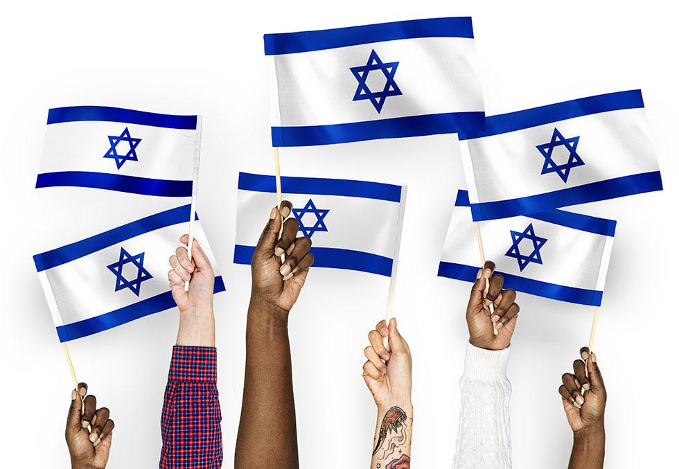 Hands waving flags of Israel