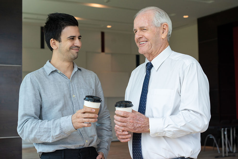 Happy colleagues with take away coffee
