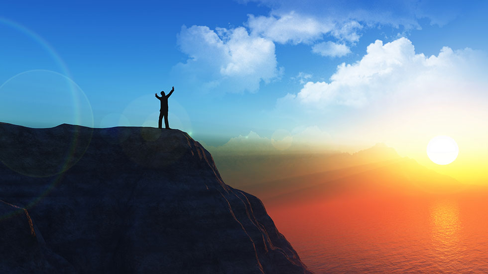 3D male figure on the top of a cliff with his arms raised in suc