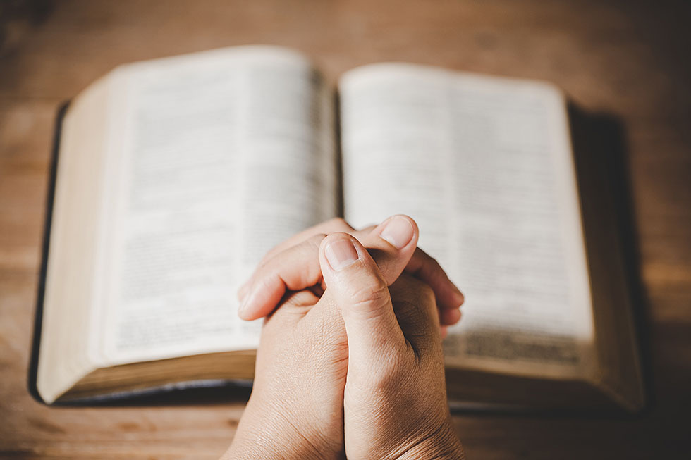 Spirituality and religion, Hands folded in prayer on a Holy Bibl