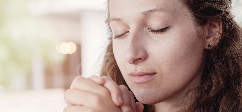Young woman praying with eyes closed