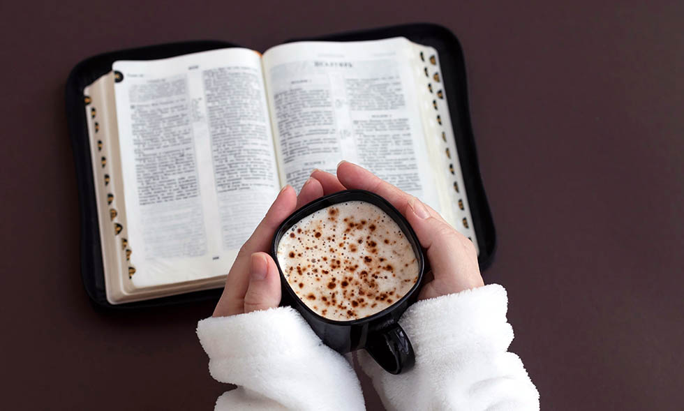 Woman hand holding cup of coffee and reading Holy bible.