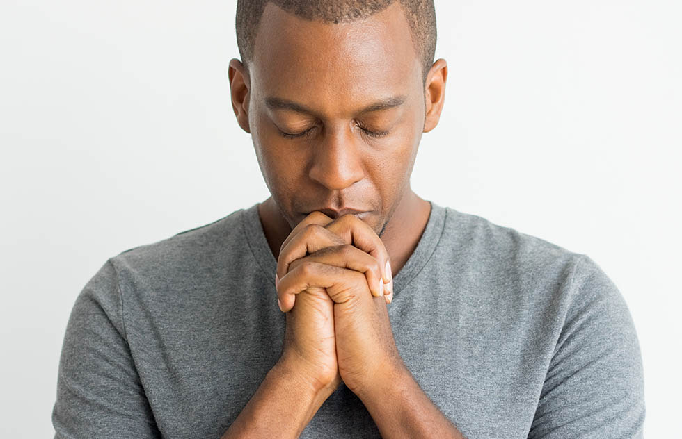 Calm spiritual handsome African guy praying with closed eyes