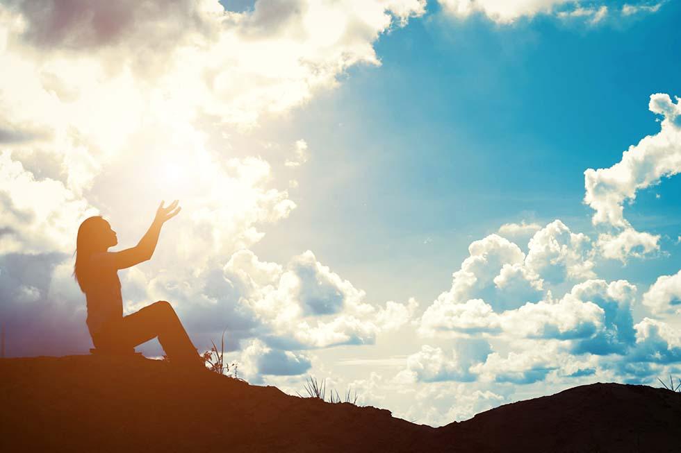 женщина молится на фоне неба