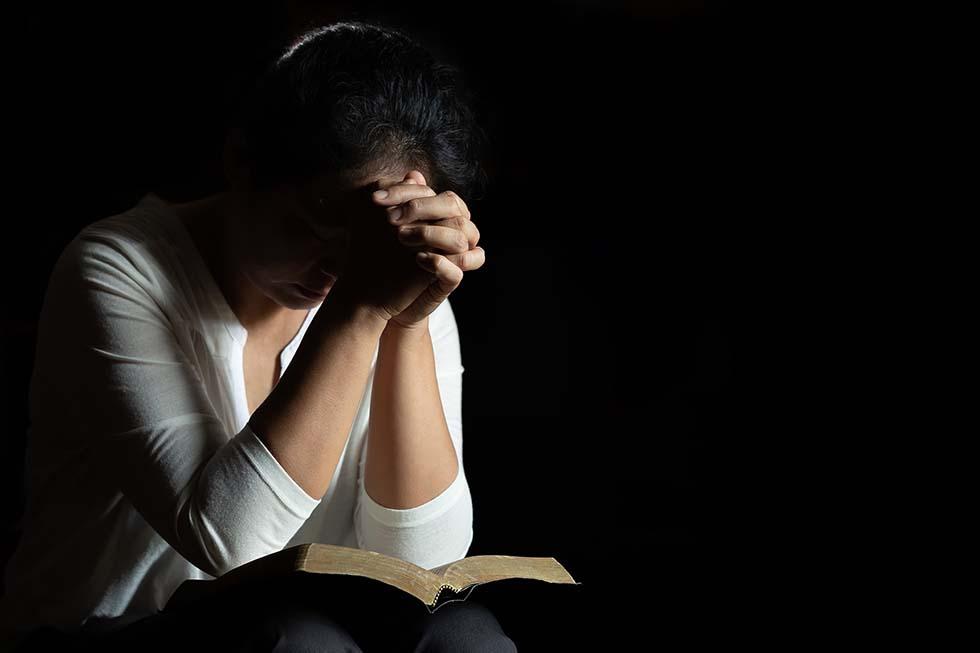 женщина молится над Библией