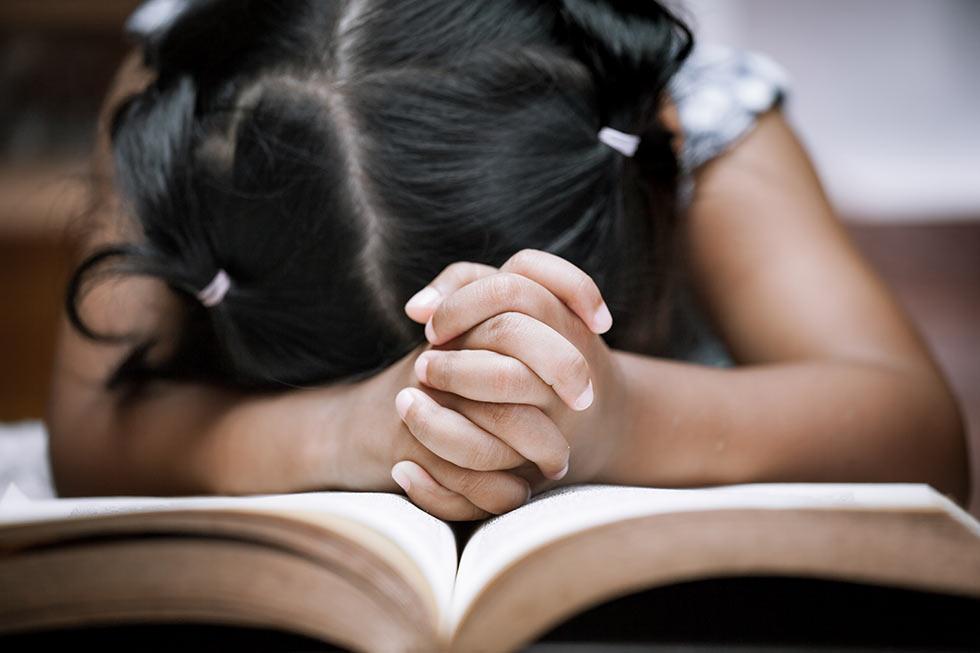 девочка молится над Библией