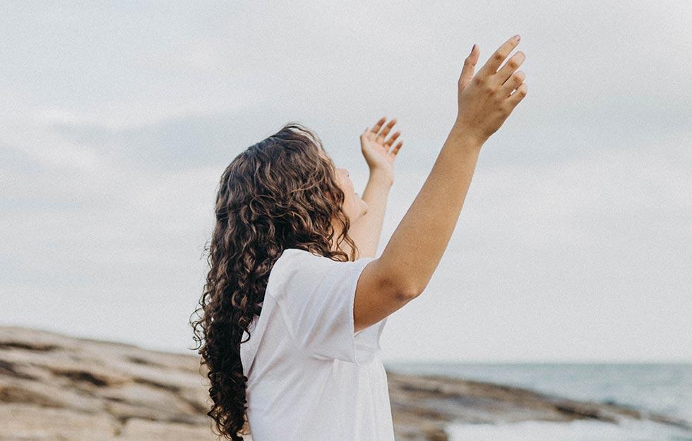 девушка поднимает руки к Богу